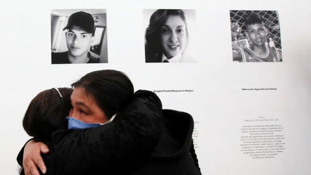 Dos madres de víctimas de las protestas contra la brutalidad policial se abrazan frente a las fotos de sus hijos, 2 de junio de 2021