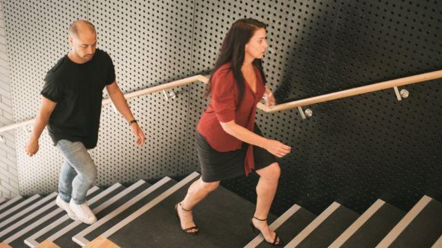 Una mujer sube las escaleras rápidamente y un hombre la sigue detrás