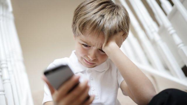 niño mirando celular con gesto de preocupación