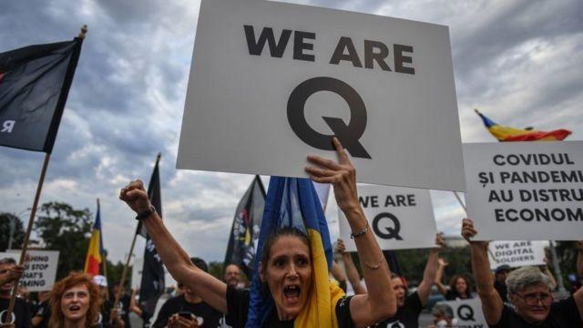 Mulher com cartaz em que se lê: Somos o Q
