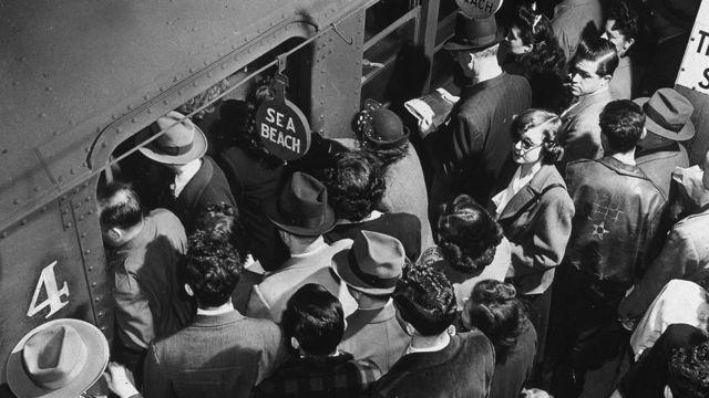 Los pasajeros de la hora pico que abordan el tren subterráneo de Sea Beach desde una plataforma abarrotada en Times Square en la ciudad de Nueva York