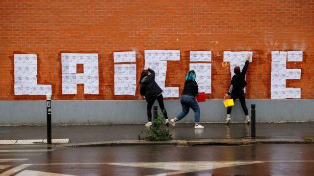 Três mulheres pintam palavra laicidade em parede