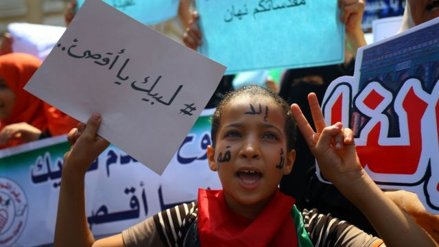 """طفلة فلسطينية تحمل لافتة كُتب عليها """"لبيك يا أقصى"""""""