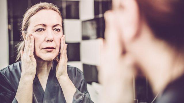 Mujer mirándose al espejo.