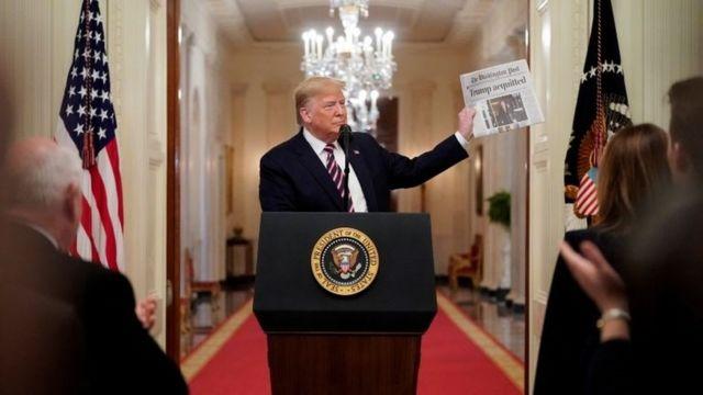 ترامب يحمل صحيفة تحمل عنوان خبر تبرئته
