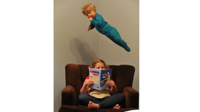 Will en el aire como si estuviera volando sobre su hermana sentada en un sillón leyendo un libro