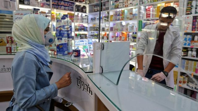 Mulher usando máscara em farmácia em Teerã no dia 24 de fevereiro