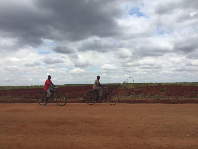 Chicos montando en bicicleta frente a terrenos baldíos.