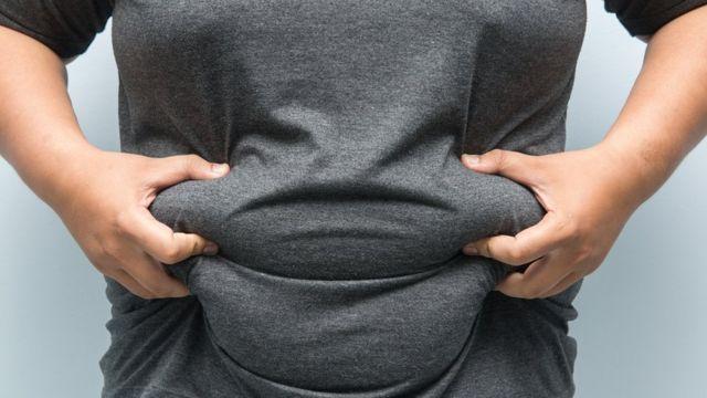 Homem segura sua barriga