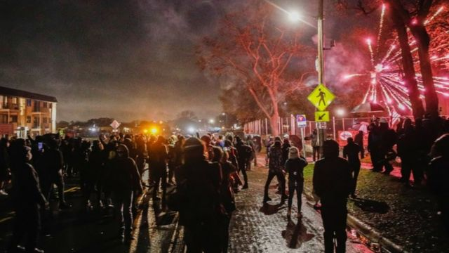 Protesters throw fireworks towards police outside Brooklyn Center Police Department a day after Daunte Wright was shot and killed by a police officer