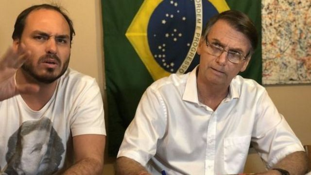 Carlos Bolsonaro e Jair Bolsonaro sentados à mesa durante transmissão ao vivo de vídeo
