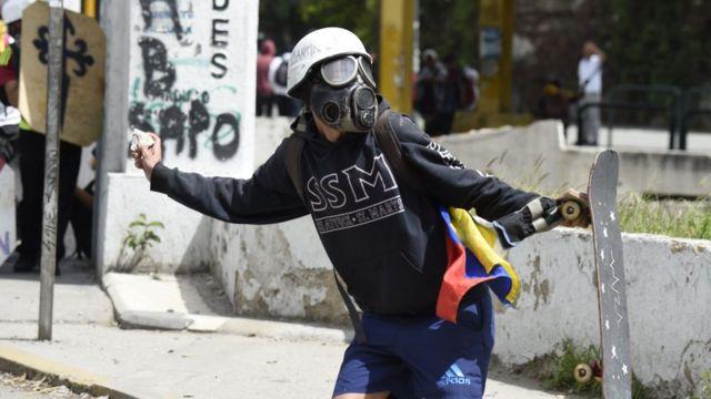 Un manifestante lanza una piedra contra miembros de las fuerzas de seguridad en Venezuela.