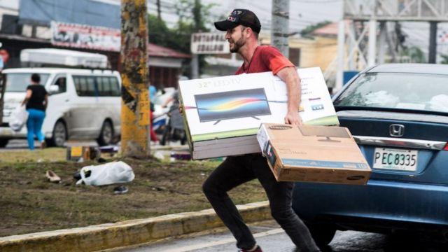 Un hombre transporta una televisión.
