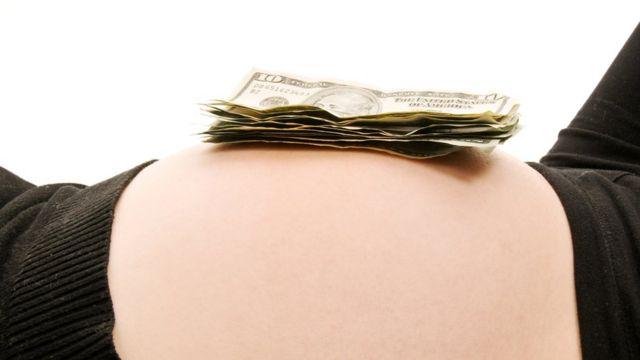Barriga de embarazada con billetes de dólares encima.