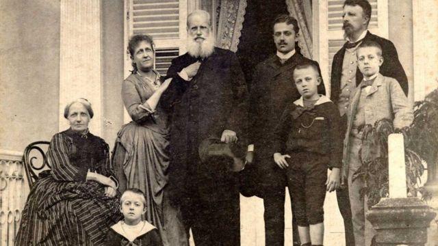 Família imperial posa em escadaria, em frente a casa