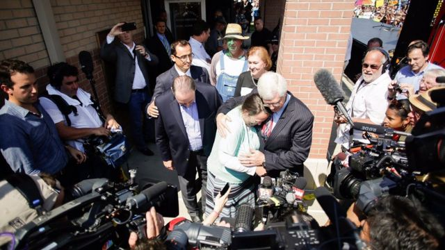 Rowan County clerk Kim Davis, center, hugs her attorney, Mat Staver, with Republican presidential candidate Mike Huckabee, centre left, next to her after being released from the Carter County Detention Center, 8 September in Grayson, Ky.