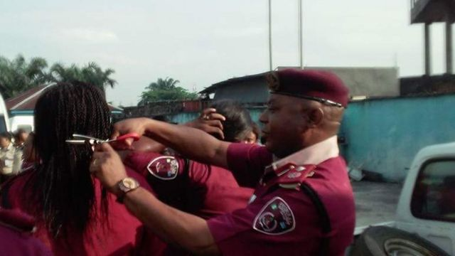 Man in maroon beret cuts a woman's hair in public