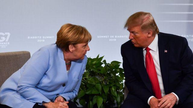 المستشارة الألمانية أنجيلا ميركل (إلى اليسار) والرئيس الأمريكي دونالد ترامب يتحدثان خلال اجتماع ثنائي في بياريتز، جنوب غرب فرنسا في 26 أغسطس 2019، في اليوم الثالث من القمة السنوية لمجموعة السبع