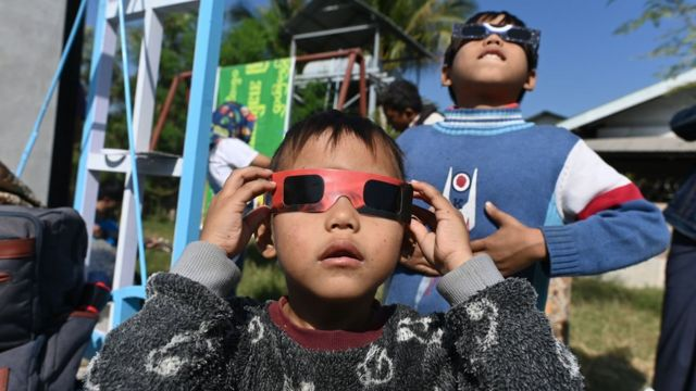 "Children uses eclipse glasses to watch a rare ""ring of fire"" solar eclipse in Wan Twin in central Myanmar on December 26, 2019"