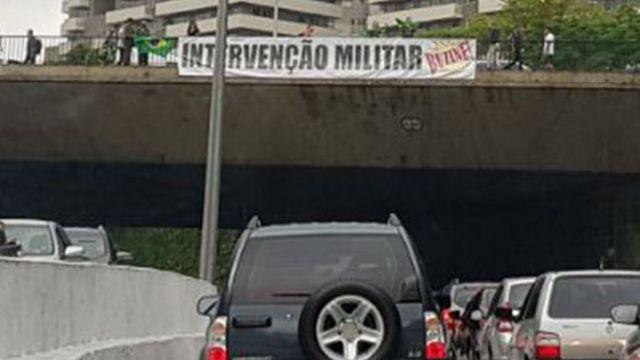 Carro na rua e ponte com faixa pedindo intervenção