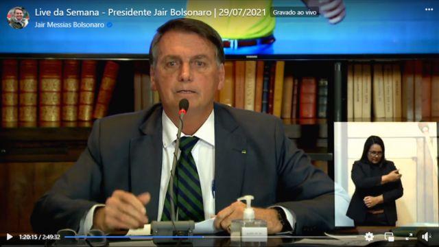 Reprodução de vídeo no Facebook mostra Bolsonaro, sentado, falando no microfone com livros atrás