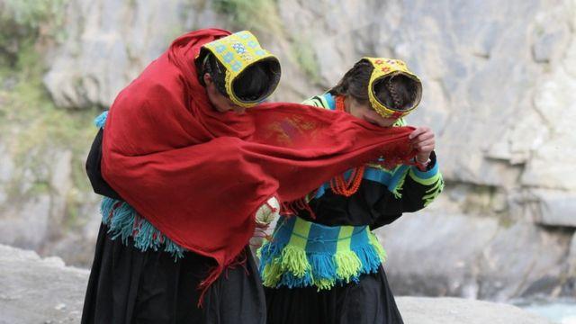 Dve žene pokrivaju lice maramom