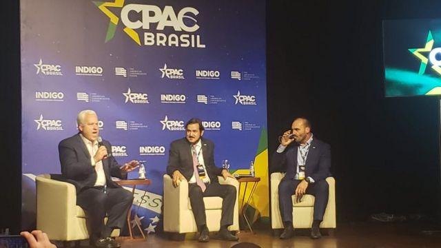 Matt Schlapp, Antônio de Rueda e Eduardo Bolsonaro sentados em mesa do evento