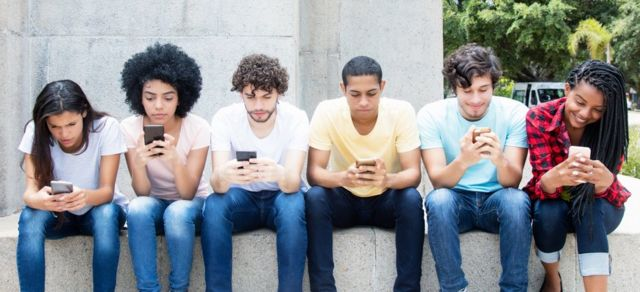 A group of young adults checking with their phones