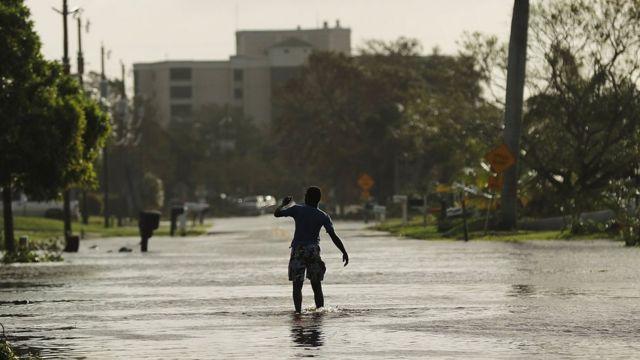 Jovem anda por rua inundada em Naples, na Flórida