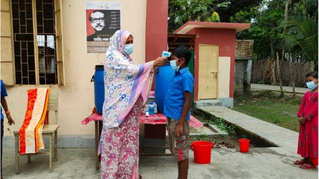 একটি স্কুলে প্রবেশের আগে শিক্ষার্থীদের তাপমাত্রা পরীক্ষা করে দেখা হচ্ছে