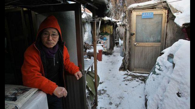 Um idoso sul-coreano sentado na comunidade de Guryong em Seul com neve no chão