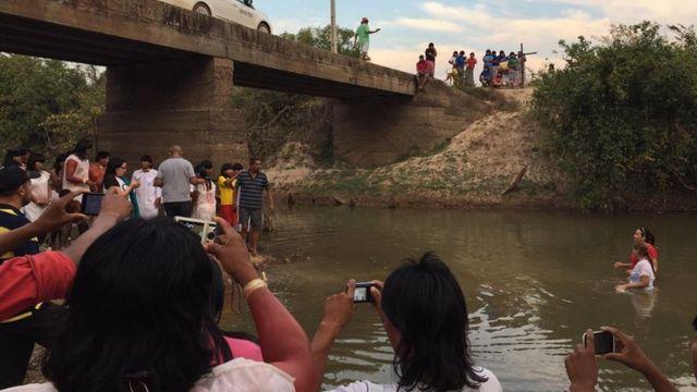 Indígenas em cerimônia de batismo em rio