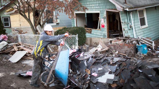 Hombre sacando escombros con una carretilla frente a una casa destruida tras el huracán Sandy