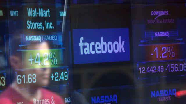 Pantalla con números y precios de acciones más el logo de Facebook.