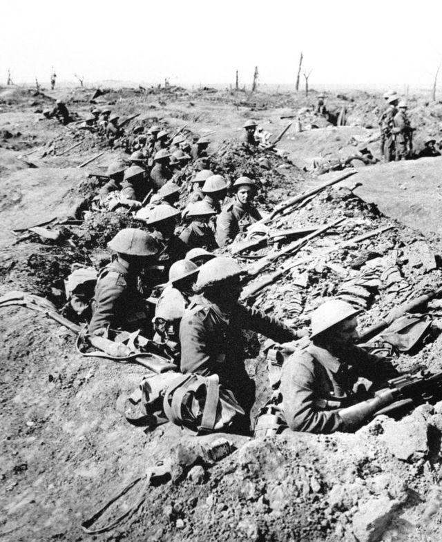 La infantería británica ocupa una trinchera poco profunda, frente a un paisaje en ruinas.