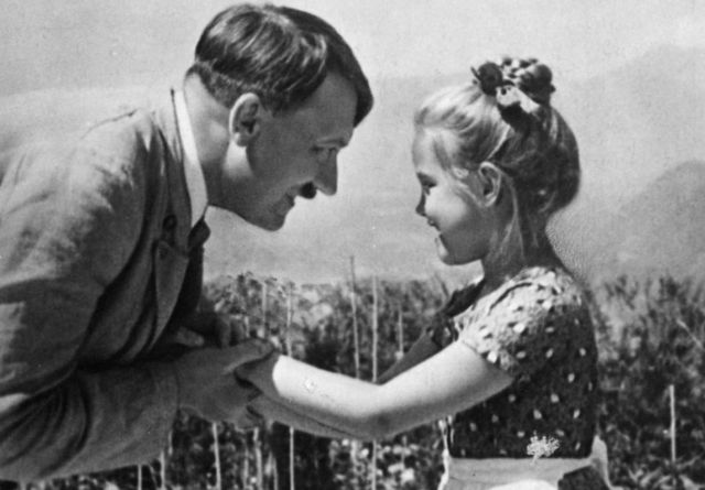 A girl, believed to be Rosa, holds Hitler's hands in a different image from the same day