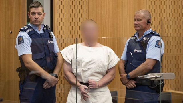 Brenton Tarrant flashed a hand sign as he appeared in court on Saturday charged with murder