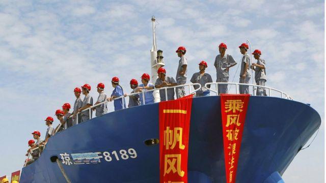 Personal uniformado con cascos rojos, parados en la cubierta de un barco pequero que se dirige a las islas Spratly.