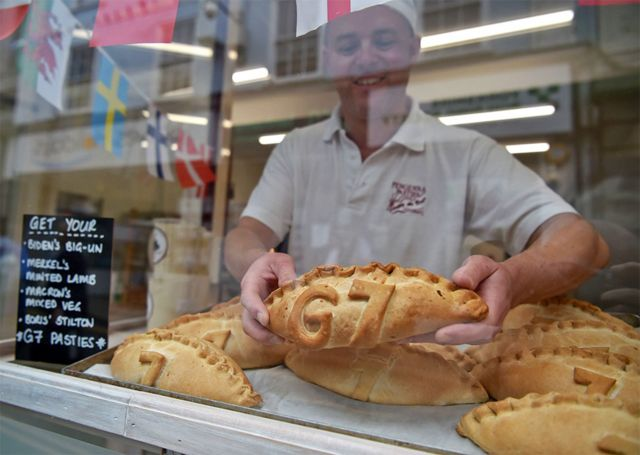 A baker puts a pasty in his shop window with G7 marked in pastry
