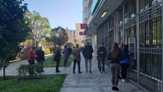 Ljudi čekaju u redu ispred banke