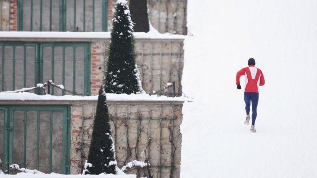 Un hombre corre en la nieve.