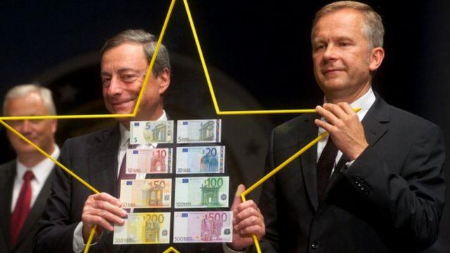 Президент Европейского Центробанка Марио Драги (слева) держит европейскую звезду вместе с президентом Банка Латвии Илмаром Римшевичем (справа) в Латвии в 2013-м году.