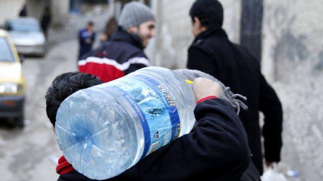 طفل يحل عبوة مياه في ضاحية دمر في دمشق