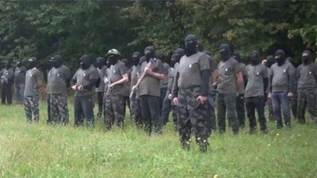 Члени угруповання в масках зі зброєю біля лісу