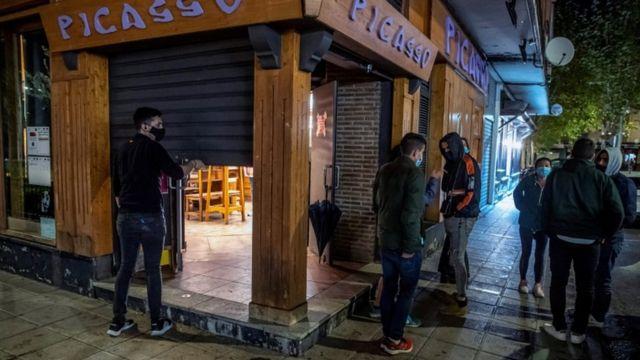 Un hombre cierra un comercio en Toledo, España.