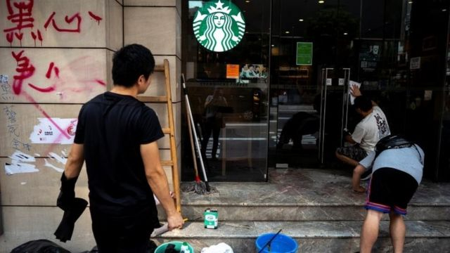 A worker cleans graffiti at a Starbucks coffee shop in Hong Kong on 30 September