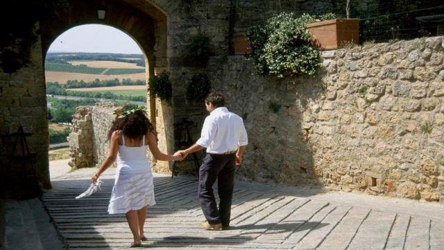 Una pareja caminando por una calle en un pueblo italiano