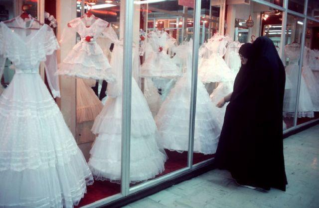 Duas mulheres com xadores pretos olham para vitrine com vestidos de casamento, em 1986