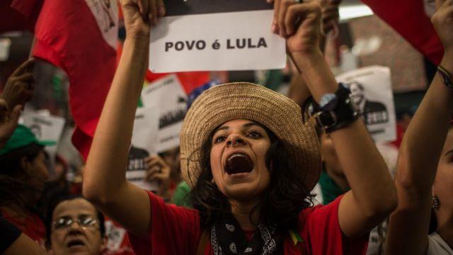 """Seguidora de Lula da Silva con un papel que dice """"el pueblo es Lula""""."""