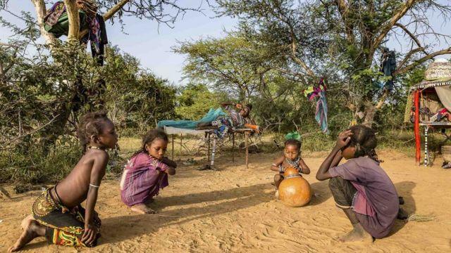 Wasu yara na wasan kasa yayinda da iyayensu ke kwance Children play in the sand as their mother wakes up.